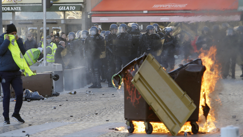 08.12.2018, Frankreich, Marseille: Die Polizei steht hinter einer brennenden Mülltonne. Bei den Demonstrationen der «Gelben Westen» in Paris hat sich die Lage am Samstagnachmittag zugespitzt. Die Polizei setzte Tränengas und Wasserwerfer ein. Nach An