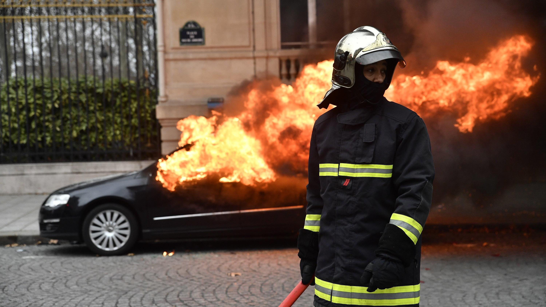 08.12.2018, Frankreich, Paris 8th (8th Arrondissement Of: Ein Mitglied der Feuerwehr steht während der Proteste und Unruhen in Paris vor einem brennenden Auto. Bei Protesten der «Gelbwesten» sind am Samstagvormittag in Paris mehrere Hundert Menschen