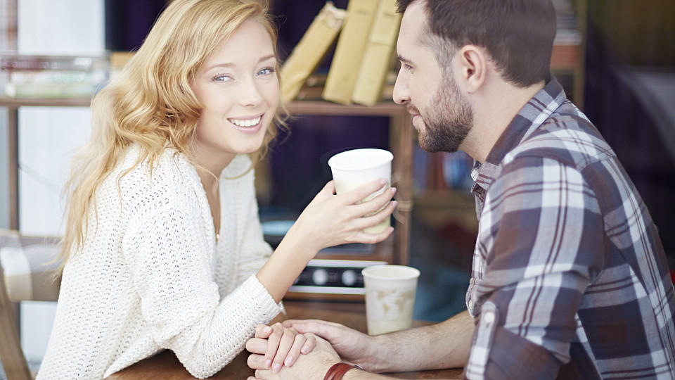 Young beautiful couple drinking coffee at cafe