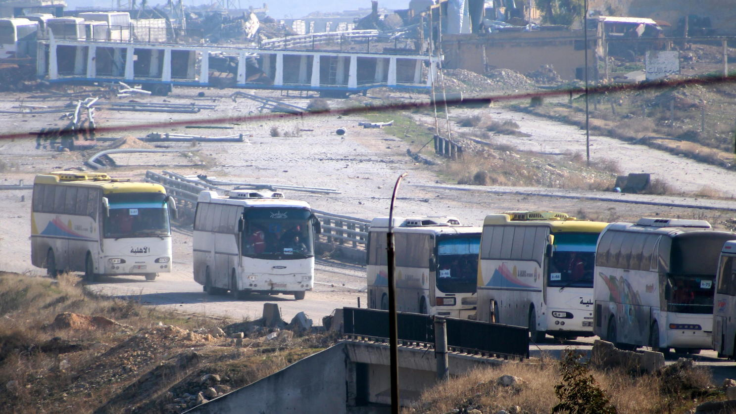 epa05682207 Buses carrying a group of fighters and their families leave eastern neighborhoods of Aleppo, Syria, 19 December 2016. Reports state at least 4,500 people have left government-besieged areas in the northern Syrian city of Aleppo since the