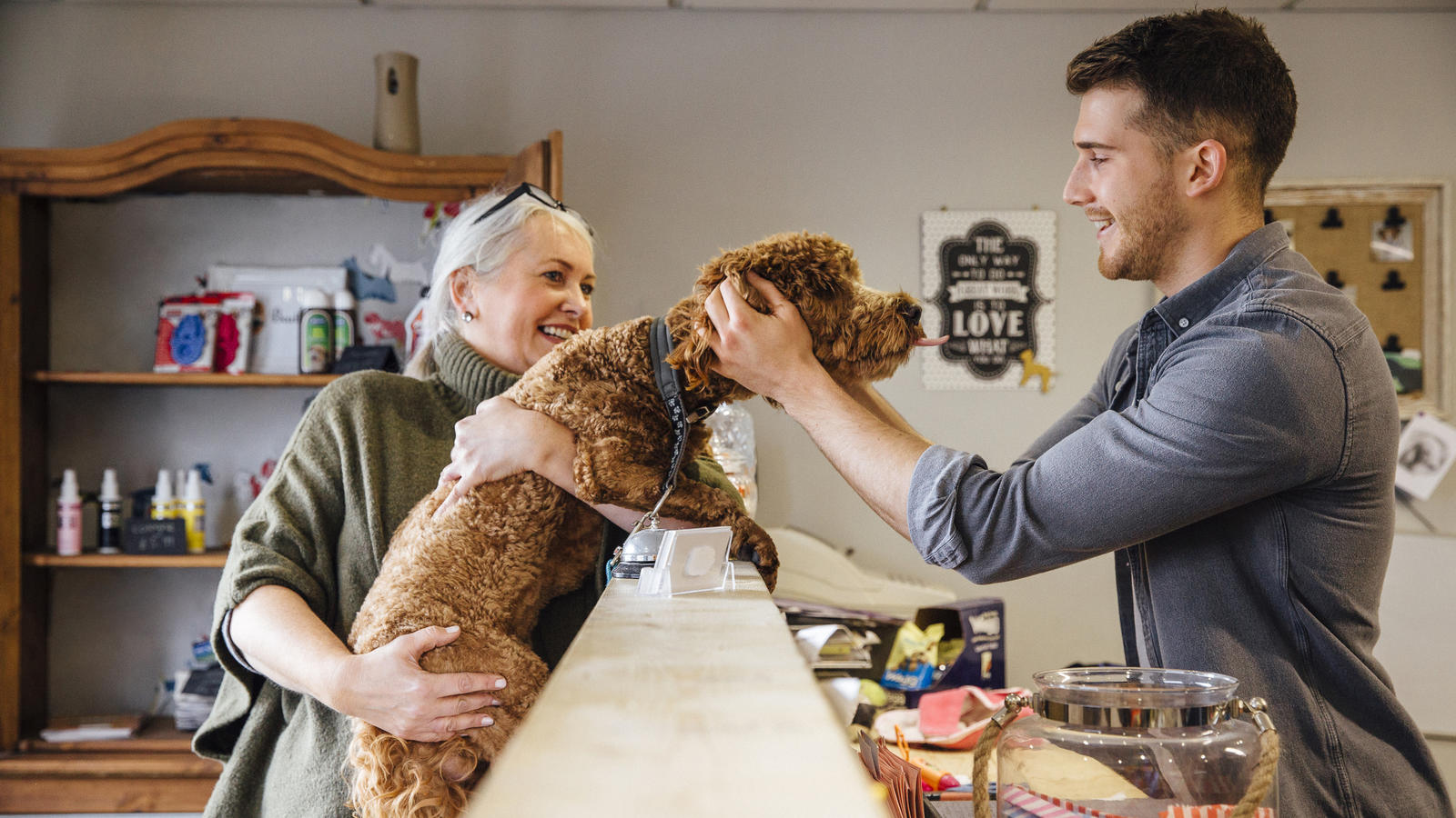 Mature woman is at the reception in the dog grooming salon with her pet cockapoo. The dog is leaning over the counter to recieve affection from the dog groomer.