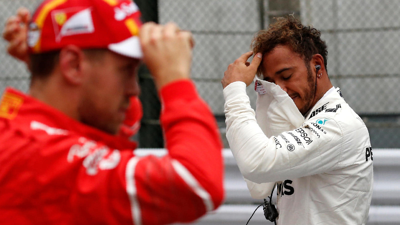 Formula One F1 - Japanese Grand Prix 2017 - Suzuka Circuit, Japan - October 7, 2017. Mercedes' Lewis Hamilton of Britain reacts after getting pole position in qualifying next to Ferrari's Sebastian Vettel of Germany. REUTERS/Toru Hanai