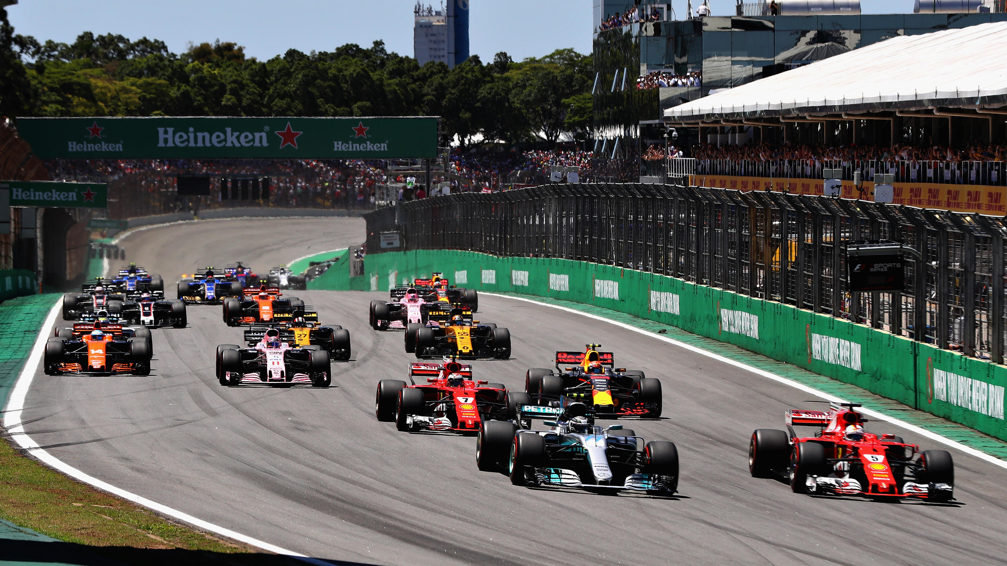 SAO PAULO, BRAZIL - NOVEMBER 12: Sebastian Vettel of Germany driving the (5) Scuderia Ferrari SF70H and Valtteri Bottas driving the (77) Mercedes AMG Petronas F1 Team Mercedes F1 WO8 lead the field towards turn one at the start during the Formula One