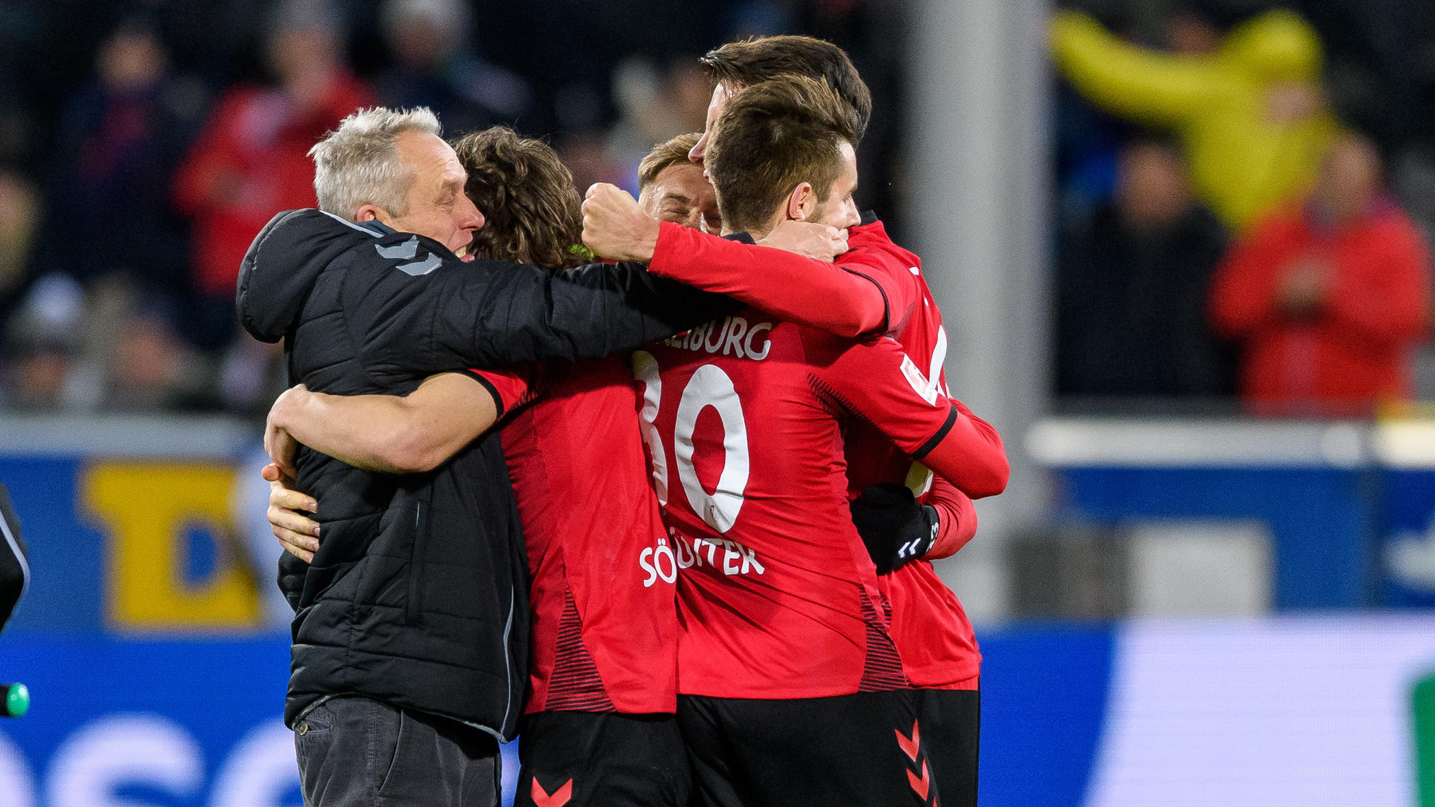 FREIBURG IM BREISGAU, GERMANY - DECEMBER 12: Head coach Christian Streich of Freiburg celebrates the victory with his players during the Bundesliga match between Sport-Club Freiburg and Borussia Moenchengladbach at Schwarzwald-Stadion on December 12,