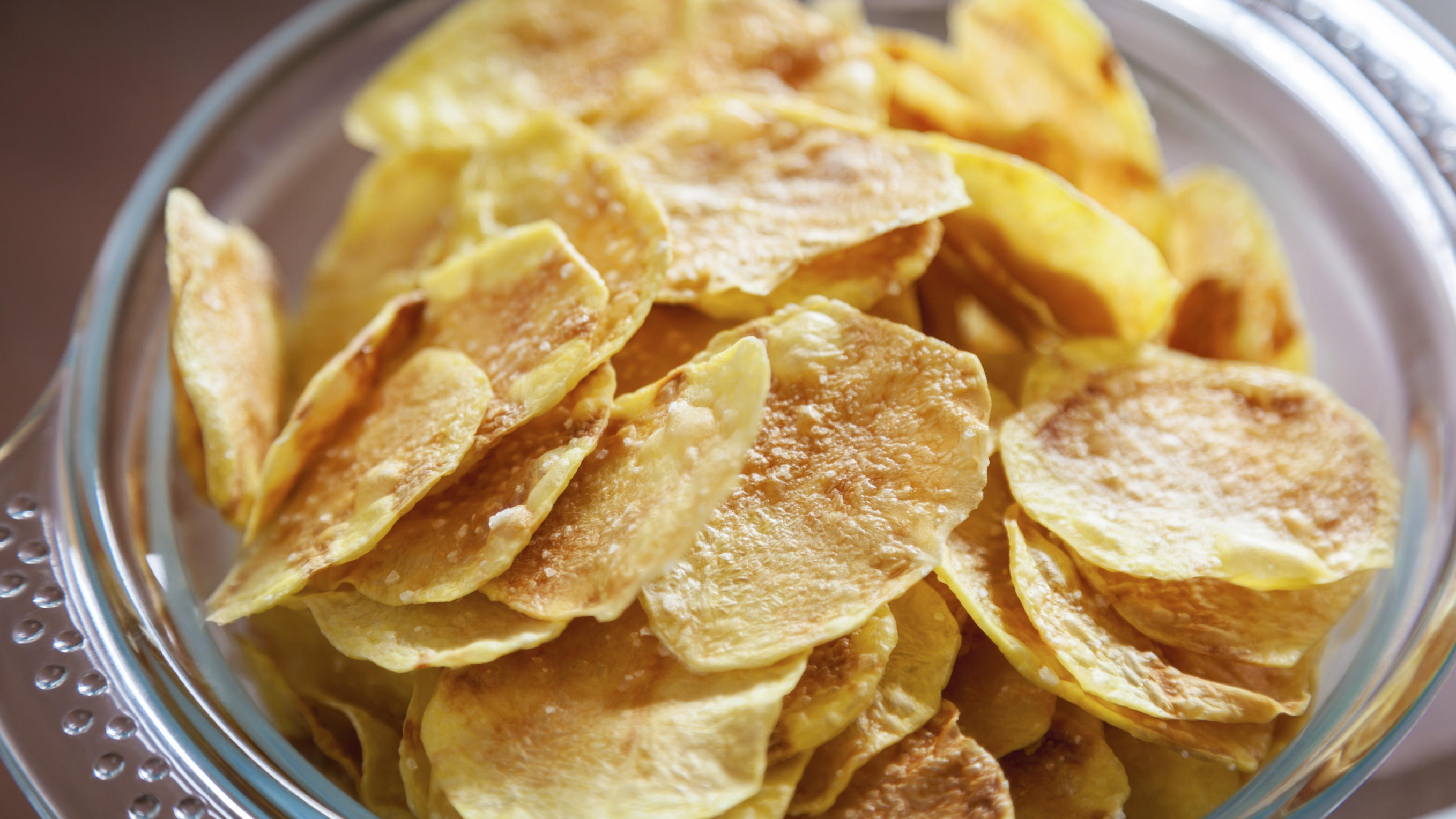 Delicious homemade potato chips in a glass bowl